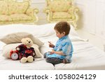 Small photo of Boy with happy face puts favourite toy on bed, time to sleep. Kid put plush bear near pillows and alarm clock, luxury interior background. Child in bedroom with silence gesture. Time to sleep concept.