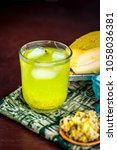 Small photo of Close up of Kari ka ras or Mango juice with all its ingredients in a transparent glass on wooden surface in dark Gothic colors.