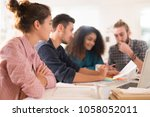 in the office. meeting around a ... | Shutterstock . vector #1058052011