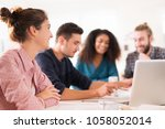 in the office. meeting around a ... | Shutterstock . vector #1058052014
