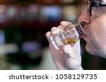 man sampling whisky from a... | Shutterstock . vector #1058129735