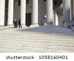 Small photo of A well dressed man and woman converse on the steps of a legal or municipal building. Could be politicians, business or legal professionals.