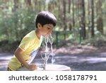 kid drinking water. outdoor... | Shutterstock . vector #1058178791