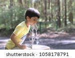 Kid Drinking Water. Outdoor...