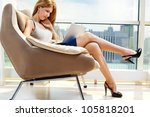 Young Woman Sitting On Chair...