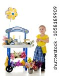Small photo of An adorable preschooler looking pleased while holding a wad of money by her flower-vending stand. The stand's signs are left blank for your text. On a white background.