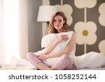 young woman holding a pillow... | Shutterstock . vector #1058252144