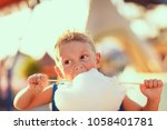 young boy standing and biting... | Shutterstock . vector #1058401781
