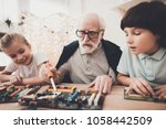 Small photo of Grandfather, grandson and granddaughter at table at home. Grandpa teaches children how to braze.