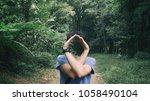 a man standing in green forest... | Shutterstock . vector #1058490104