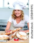 Cheerful female cook posing in kitchen. Preparing delicious baguettes - stock photo