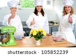 Professional female chefs showing thumbs up. Shot in kitchen - stock photo