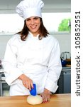 Uniformed female chef in a restaurant or hotel kitchen - stock photo