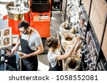 two sellers in uniform filling... | Shutterstock . vector #1058552081