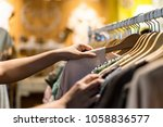 Small photo of Close up of woman hand choosing thrift young and discount t-shirt clothes in store, searching or buying cheap cotton shirt on rack hanger at flea market , stall shopping apparel fashion concept