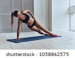 Small photo of Confident in her fitness regime. Beautiful young woman in sport clothing keeping side plank pose while exercising in the gym