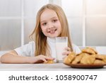 smiling little girl is sitting... | Shutterstock . vector #1058900747