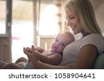 cheerful mother with baby boy... | Shutterstock . vector #1058904641