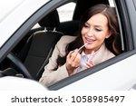 pretty woman driver doing makeup | Shutterstock . vector #1058985497