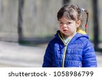 unhappy little girl wearing a... | Shutterstock . vector #1058986799