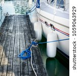 Small photo of Anchored boat and wooden pier, Toronto, Canada