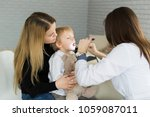 Small photo of Doctor examine child's throat. Boy and mother at pediatrician office.