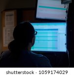 Small photo of nurse, medical professional in silhouette, looking at monitor screens. Hospital, clinic setting in birthing suite.