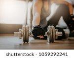 woman picking up dumbbell on... | Shutterstock . vector #1059292241