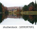 a glassy lake mirroring fall...   Shutterstock . vector #1059397091