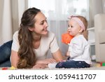 a young mother plays with a... | Shutterstock . vector #1059411707