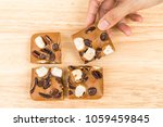 female hand picking blondies...   Shutterstock . vector #1059459845