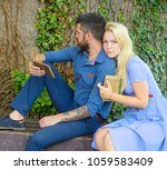 Small photo of Couple in love hugs outdoor, nature background, defocused. Romantic couple holds old book with poems about love. Girl with pensive face listen bearded man reading poems. Romantic vintage date concept.