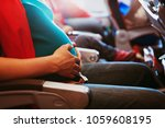 pregnant woman travel by plane | Shutterstock . vector #1059608195