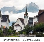 Elegant church in the middle of Morschach, Switzerland, on a rainy day with low hanging clouds