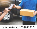 Small photo of messenger man hold box and talk on smart phone and payment terminal in hands, Package delivery concept