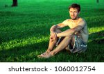 man sitting on the grass in a... | Shutterstock . vector #1060012754