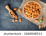 Small photo of Top view of almonds on dark stone table with wood spoon or scoop. Almond in wooden bowl. Nuts freely laid on dark board.