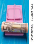 Small photo of in a pink mousetrap bait euro money, the concept of danger and trust in finance, on blue boards