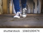 female legs in canvas shoes... | Shutterstock . vector #1060100474