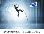 businessman jumping over tax in ... | Shutterstock . vector #1060136417