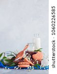 Small photo of Oatmeal cookies with milk, sugar and flour on a kitchen table. Balking supplies with copy space. Kitchen still life with spring flowers and green leaves.
