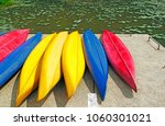 A Row Of Colorful Canoe Parked...