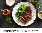 Small photo of Juicy steak medium rare beef with green salad on white plate over black stone table. Top view, flat lay