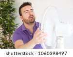 young man sweating because... | Shutterstock . vector #1060398497