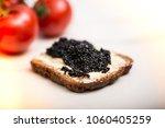black caviar on a slice of bread | Shutterstock . vector #1060405259