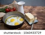 fried eggs in a frying pan with ... | Shutterstock . vector #1060433729
