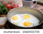 fried eggs in a frying pan with ... | Shutterstock . vector #1060433735