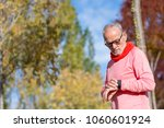 portrait of a senior man using... | Shutterstock . vector #1060601924