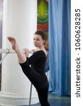 Small photo of Young woman doing stretching legs with barre in a studio