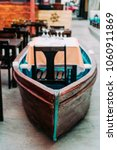 Small photo of Unusual restaurant interior: dining table in the colorful fish boat. Marine ambience